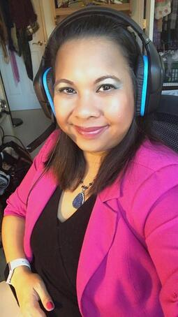 Rowena at desk with headphones and pink blazer
