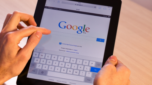 Person holding a tablet to search on Google