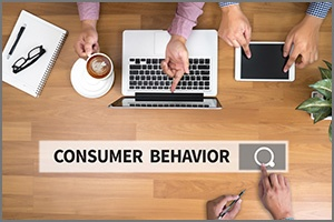 desktopo with people at laptops and sign that reads consumer behavior
